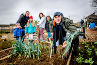 From left - Vicky Jones, Zacharie, Noella, Dylan and Lewis look on as OneFamily customer Tony Reed harvests some leeks from Westfield Allotments.